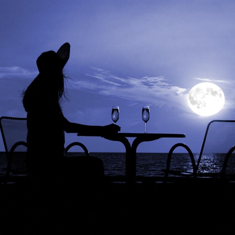 kobieta na plaży na tle księżyca w pełni