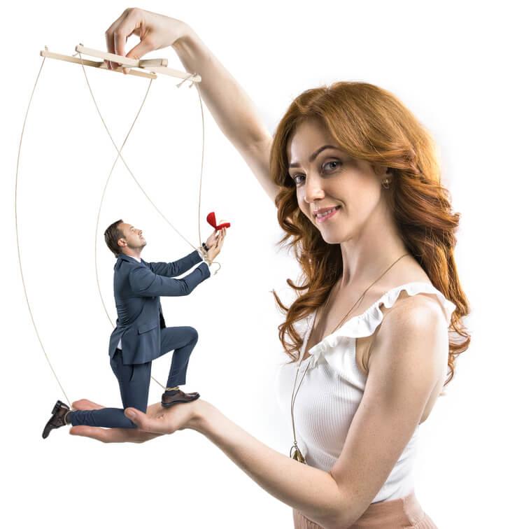 kobieta trzyma mężczyznę jak marionetkę