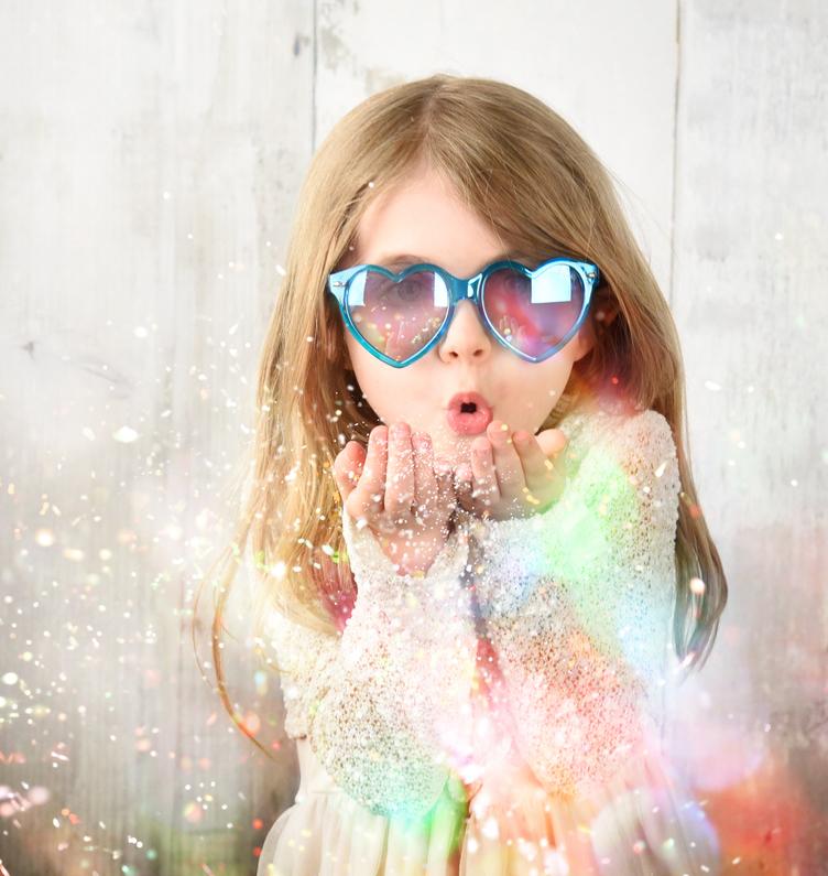 dziewczynka w okularach dmucha w pył
